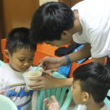 Mr. Rosario feeding one child in the Salapan Puericultural Center.